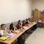Uczniowie siedzą przy stolikach i jedzą posiłek