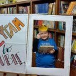 """Chłopiec z książką pozuje przy napisie """"Czytam bo lubię"""". Nad głową trzyma papierową koronę"""