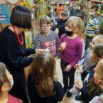 Pani bibliotekarka rozmawia z dziećmi w szkolnej bibliotece