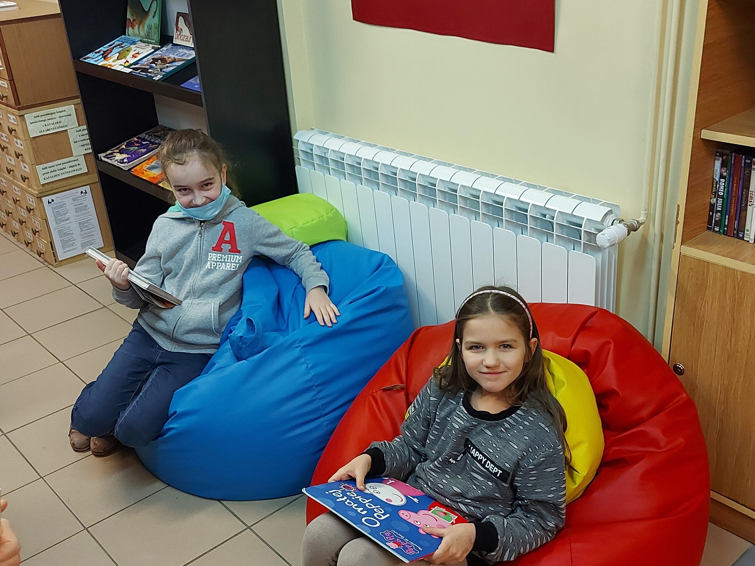 Dziewczynki siedzą na workach do siedzenia w bibliotece
