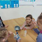 Dzieci siedzą przy stoliku. Do balonu przy użyciu lejka wsypują sodę oczyszczoną