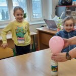 Zachwycone dzieci patrzą jak balon nałożony na butelkę rośnie