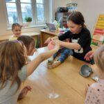 Grupka dziewczynek zakłada balon z sodą oczyszczoną na butelkę z octem