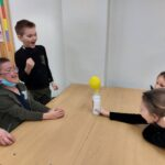 Uczniowie ze zdziwieniem i radością obserwują, jak balon założony na butelkę nabiera kształtów.