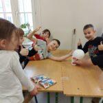 Szczęśliwi uczniowie pozują przy butelce z nadmuchanym balonem