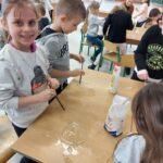 Uśmiechnięta uczennica prezentuje efekty swojej pracy - zamknięcie bańki w bańce. W oddali widać pozostałych uczniów, którzy próbują sprostać zadaniu.
