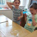 Dziewczynka i chłopiec wyrażają zachwyt z powodu udanego eksperymentu- zamknięcia dwóch baniek w jednej, większej bańce.
