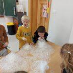 Grupa chłopców wyraża zachwyt z powodu powstałego dużego wulkanu bąbelków, który powstał na skutek dmuchania słomką do kubeczka z wodą i płynem do mycia naczyń.