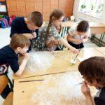 Uczniowie pracują w grupach- tworzą na ławkach szkolnych bąbelkowe wulkany.