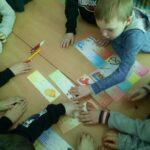 Uczniowie rozwiązują zadania z kolorowych kart z zagadkami