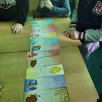 Na złączonych stolikach poukładana są kolorowe karty z zagadkami