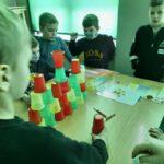Dzieci układają wieżę z plastikowych kubeczków według podanego wzoru.