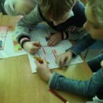 Dzieci rozwiązują zagadkę wyszukując słowa w wykreślance