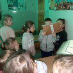 Chłopiec stojący wśród dzieci odczytuje zagadkę.