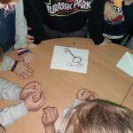Grupa dzieci stoi dookoła stołu a na środku leży klucz