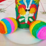 Kolorowe wydmuszki ze sznurka obok wiosennego wazonika