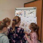 Dziewczynki przy tablicy oglądają prace plastyczne.