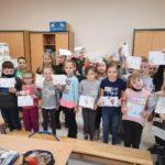 Dzieci pokazują swoje prace plastyczne.