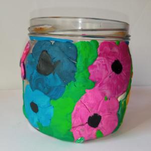 Słoik ozdobiony plasteliną, a na nim duże kwiaty w kolorze różowym i niebieskim na zielonym tle.
