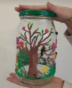 Duży słoik, a na nim wiosenna kompozycja z przyklejonej plasteliny - kwitnące drzewo, ptaki, ślimak i kwiaty w bujnej, zielonej trawie.