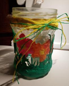 Słoik ozdobiony pomarańczowymi i różowymi kwiatami z plasteliny oraz żółtą i zieloną rafią związaną w kokardkę.