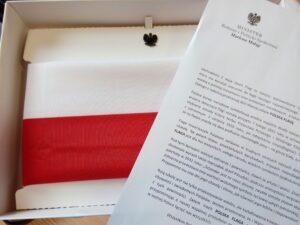 Flaga narodowa zapakowana w pudełko, nad nią przypinka z orłem w koronie. Obok list z ministerstwa.