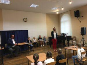 Pani Maria Rutkowska i uczniowie PSM w Pleszewie w auli szkoły.