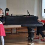 Dziewczynka gra na flecie przy akompaniamencie fortepianu