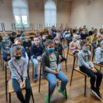 Dzieci siedzą i z uwagą słuchają koncertu