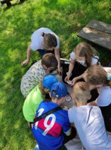 Uczniowie grają w gry siedząc na trawie