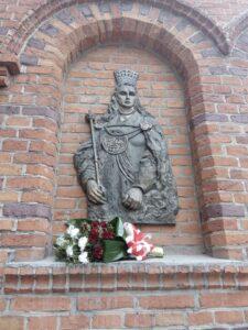 Podobizna Królowej Jadwigi z bukietem biało- czerwonych kwiatów.