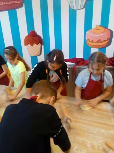 Uczniowie wałkują ciasto