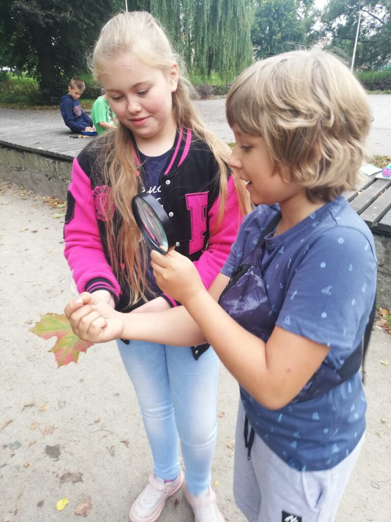 Uczniowie obserwują liść za pomocą lupy