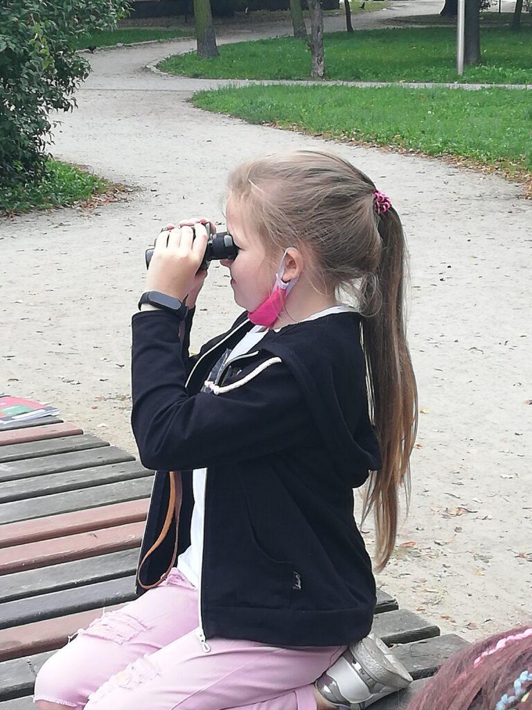Uczennica obserwuje otoczenie za pomocą lornetki