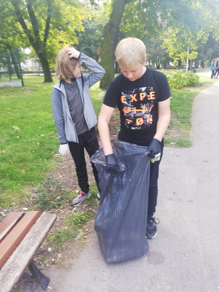 Uczniowie sprzątają śmieci do worka