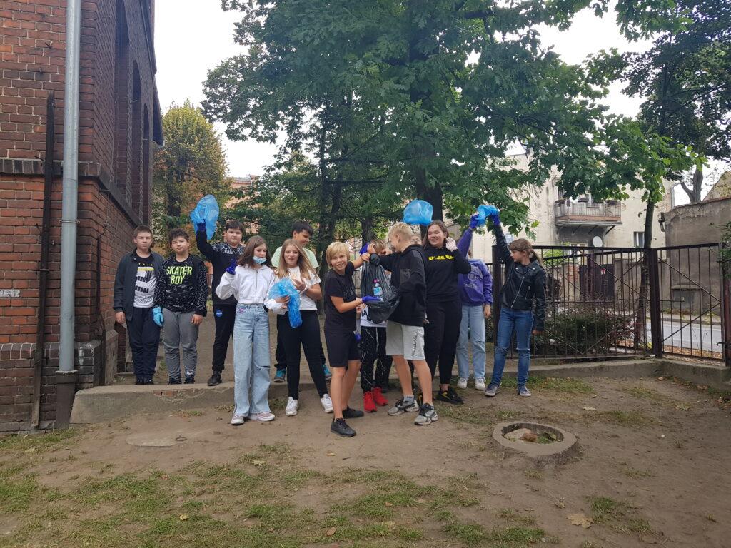 Uczniowie stoją przed szkołą z workami na śmieci