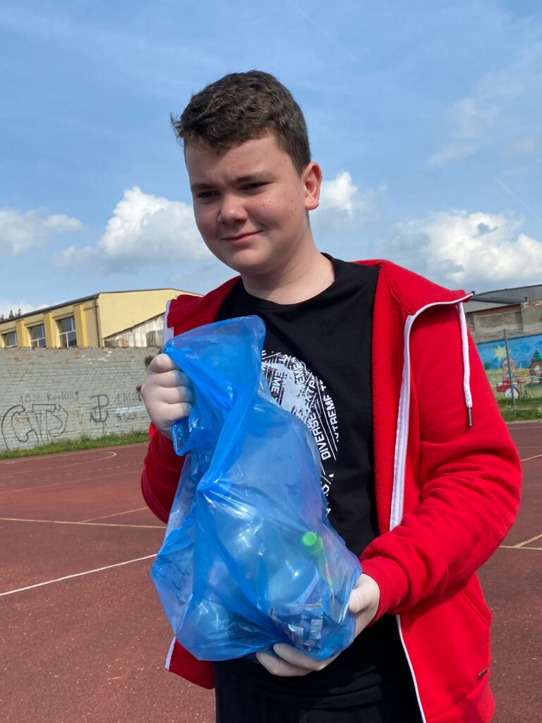 uczeń z workiem śmieci