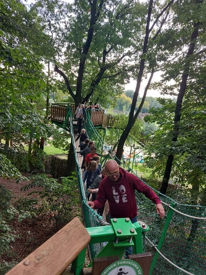 Grupa uczniów z przewodnikiem przechodzi mostkiem pomiędzy platformami na drzewach