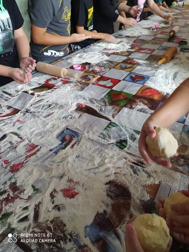 Uczniowie wałkują ciasto na ciasteczka