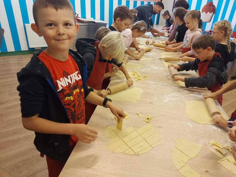 Uczniowie zawijają chruściki i wałkują ciasto
