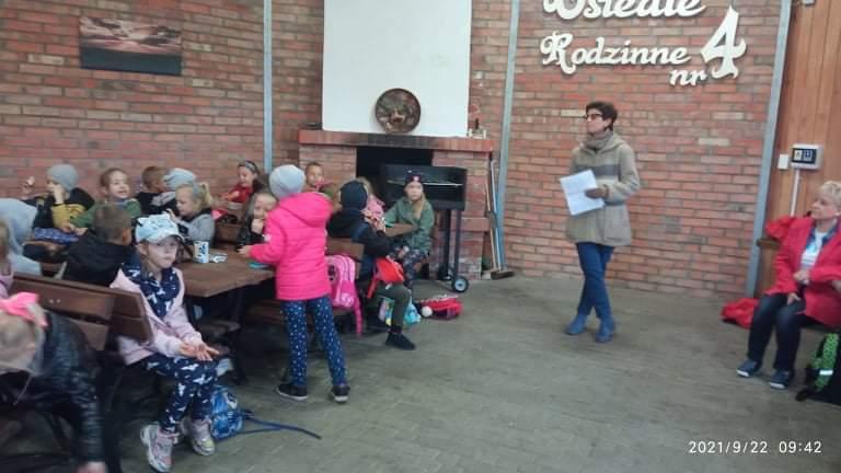 Uczniowie siedzą przy stolikach i słuchają nauczycielki