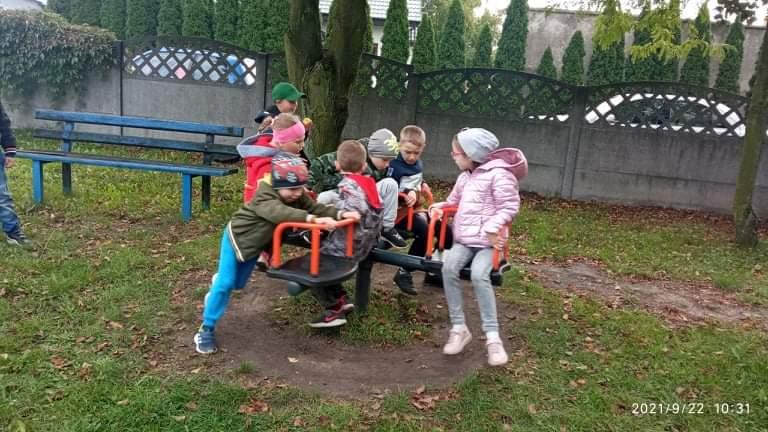 Uczniowie kręcą się na zabawce na placu zabaw